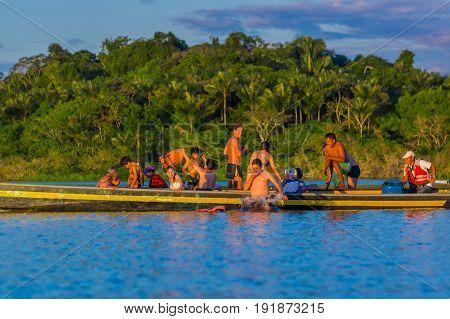 CUYABENO, ECUADOR - NOVEMBER 16, 2016: Young Tourists Jumping Into The Lagoon Grande Against The Sunset, Cuyabeno Wildlife Reserve, South America.