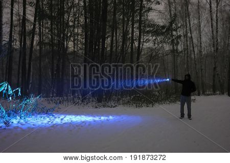 Man with electric torch stands in dark night forest during blizzard at winter
