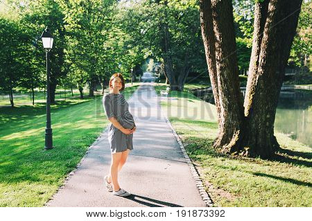 Beautiful pregnant woman in dress on nature outdoors with copy space. Expectant mother holds hands on belly on natural background of park or garden. Pregnancy expectation new life concepts.