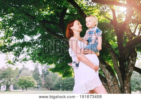 Pregnant Woman With Child Outdoors.