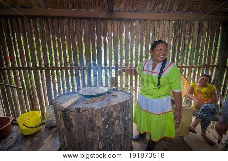LAGO AGRIO, ECUADOR - NOVEMBER, 17 2016: Woman demonstrates cooking yucca tortillas in an indoors kitchen in a Siona village in the Cuyabeno Wildlife Reserve, Ecuador.
