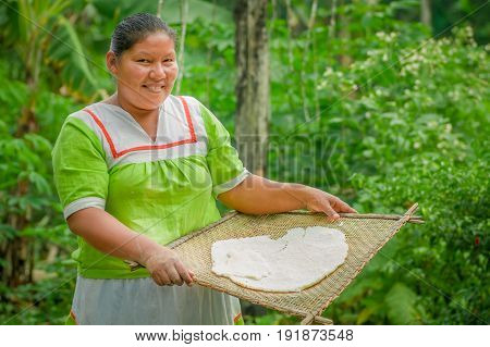 LAGO AGRIO, ECUADOR - NOVEMBER, 17 2016: Woman demonstrates cooking yucca tortillas in an outdoor kitchen in a Siona village in the Cuyabeno Wildlife Reserve, Ecuador.