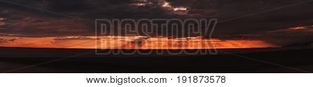 Wide panorama of stunning sunset on Black Sea during summertime with dramatic evening sky and clouds dark pebble coastline with silhouettes; Sochi Russia