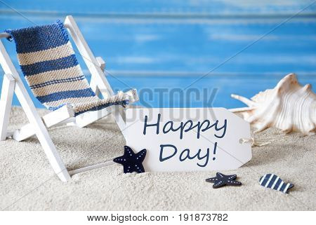 Summer Label With English Text Happy Day. Blue Wooden Background. Card With Holiday Greetings. Beach Vacation Symbolized By Sand, Deck Chair And Shell.