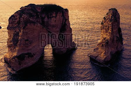 two rocks in the sea at sunset - Pigeons Rock / Sabah Nassar's Rock / Raouche in Beirut, Lebanon