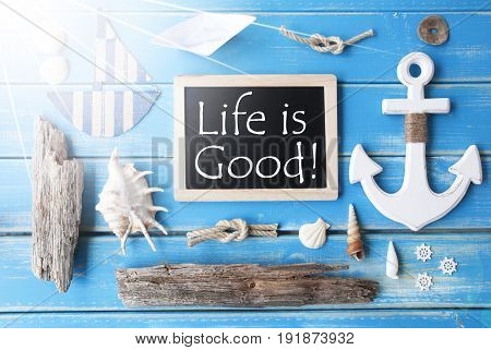Flat Lay Of Chalkboard On Blue Wooden Background. Sunny Nautic Or Maritime Summer Decoration As Holiday Greeting Card. English Quote Life Is Good