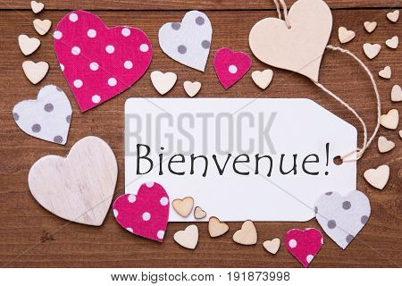 One Label With French Text Bienvenue Means Welcome. Flat Lay View With Wooden Vintage Background. Pink Wooden And Paper Hearts.