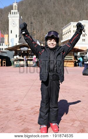 Boy in helmet and ski suit stands with raised arms and closed eyes on square in ski resort with mountains, Krasnaya Polyana, Sochi, Russia