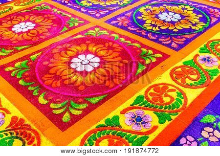 Antigua, Guatemala - April 13 2017: Closeup of floral pattern on handmade dyed sawdust carpet for Holy Thursday procession in colonial town with most famous Holy Week celebrations in Latin America