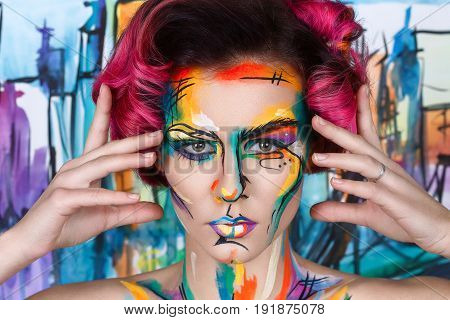 close-up fashion surrealist faceart portrait of young girl with art painting posing. Amazing creative picture with surrealistic face. Painted background. Thinking gesture