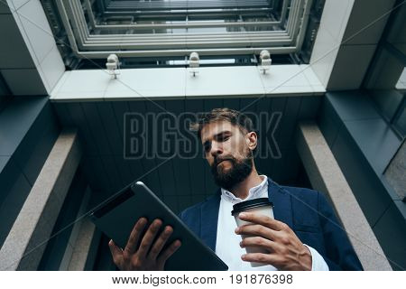 Businessman working behind a tablet, businessman with a tablet, businessman holding a glass of coffee.