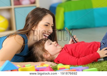 Side view of a mother and two years toddler playing with a smart phone on line lying on the floor in the bedroom at home with a colorful background