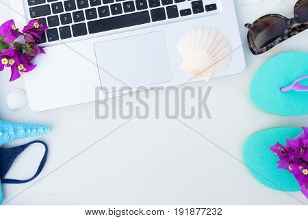 Summer beach fun mock up -laptop keyboard with blue swimming suit, sandals, sunglasses