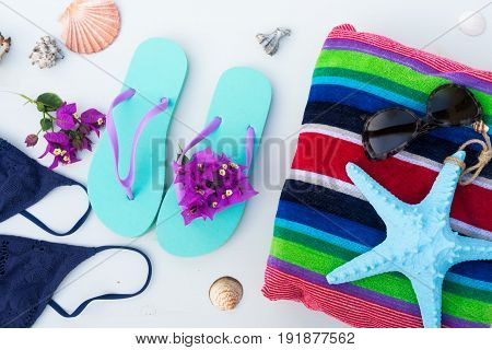 Summer beach fun - sandals with swimming suit, beach towel and starfish, top view scene