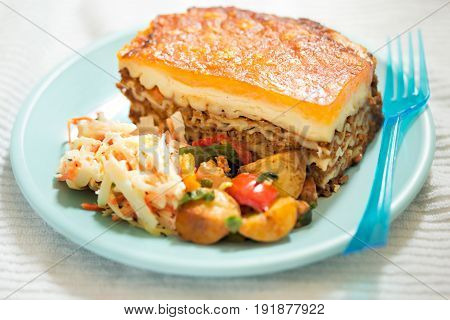 Lasagne with potato salad and coleslaw on blue plate