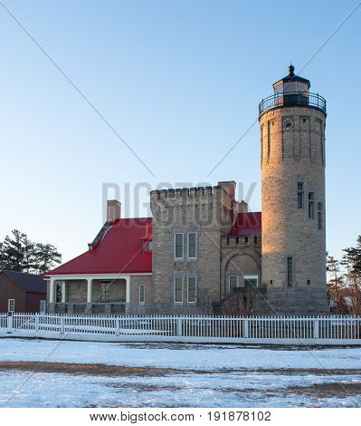 Old Mackinaw point lighthouse Michigan taken in the winter at dawn with soft warm light pouring onto the desolate cold landscape.