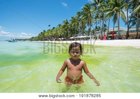 BORACAY, WESTERN VISAYAS, PHILIPPINES - MARCH 27, 2017: Wide angle view of a local child posing to the camera at White Beach.