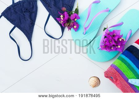 Summer beach fun - sandals with swimming suit, beach towel close up , copy space on white wooden backgroun