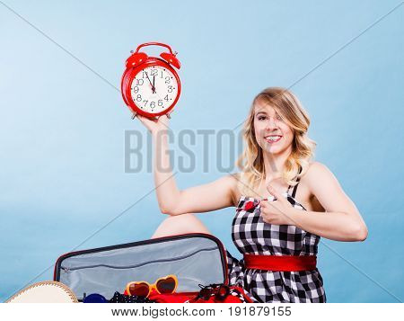 Time for travel concept. Happy woman sitting on floor with messy packed suitcase holding big red old clock