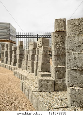 Groups of concrete pavement blocks with mineral topping stacked along unfinished path