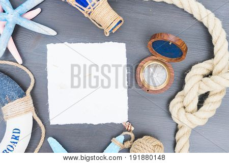 Old vintage compass with marine knot, life-ring and seastars with copy space on white paper note