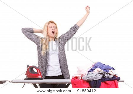 Household duties taking care of house concept. Tired yawning woman standing behind board having pile of clothes to iron