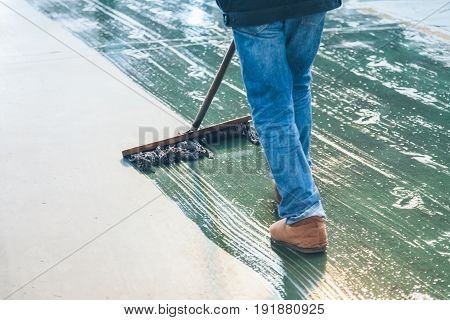 low section of male worker mopping the concrete floor in factory/warehouserear view.