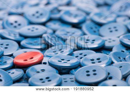 The one red button on a heap of blue buttons
