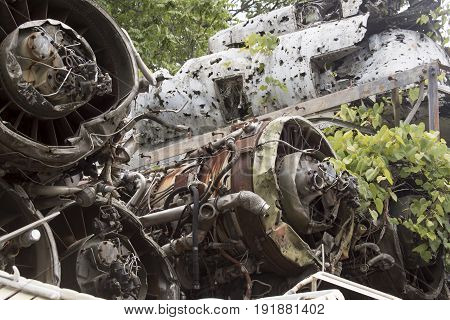 Engines and hull of wrecked airplane with weeds in junkyard.