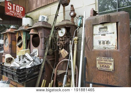 Vintage gasoline or petrol pumps rusting in junkyard.