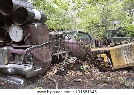 Rusting scrap metal with car and heavy equipment in junkyard.