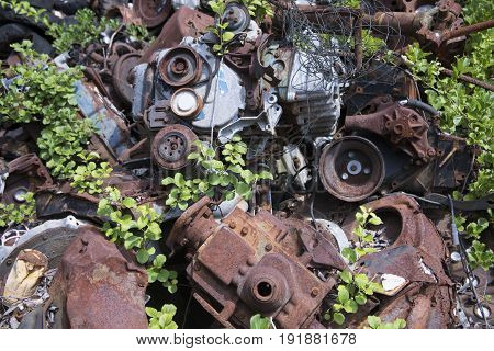 Rusting scrap metal from old cars and equipment in junkyard.