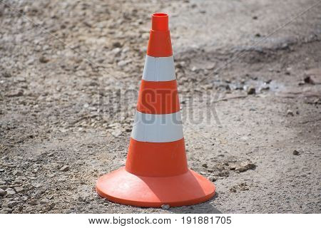 Emergency cone with orange stripes standing on the asphalt