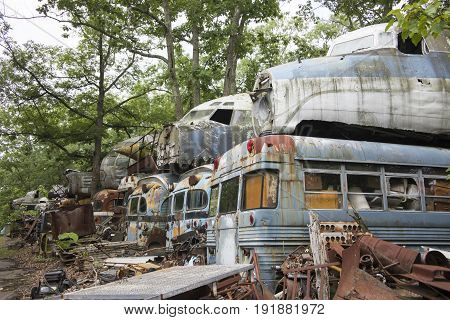 Cockpit units of wrecked military aircraft on top of transport busses in junkyard.