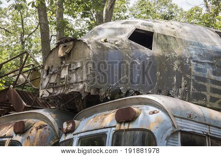 Military aircraft parts on old busses in wooded junkyard.