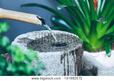 side view of bamboo spout pouring water on stone.