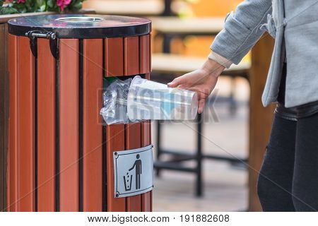 side view of man hand throw empty drinking cup into dustbin in city streetChina.