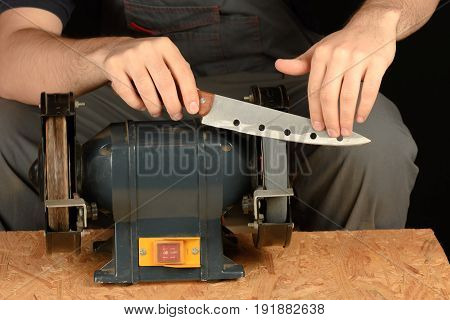 A Man In Working Clothes Sharpens Kitchen Cheese Knife