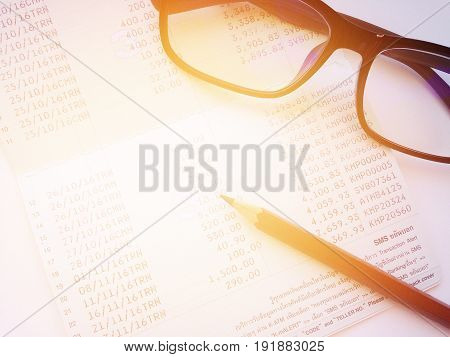 Business, finance, savings, banking or  loan concept : Pencil, eyeglasses and savings account passbook or financial statement on white background