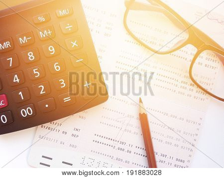 Business, finance, savings, banking or  loan concept : Pencil, eyeglasses, calculator  and savings account passbook or financial statement on white background