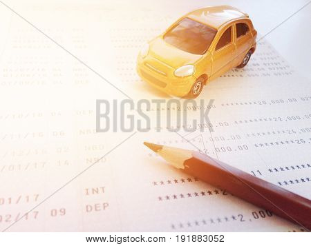 Business, finance, savings, banking or car loan concept : Miniature car model, pencil and savings account passbook or financial statement on white background