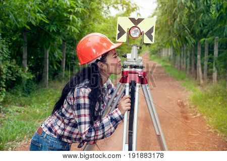 Female Surveyor or Engineer making measure by prism reflector on the street in a field.