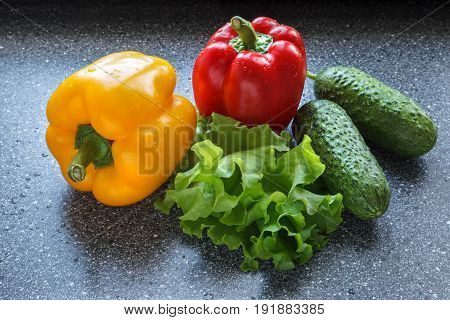 Red and yellow bell peppers, cucumbers and lettuce leaves on dark background, with water drops