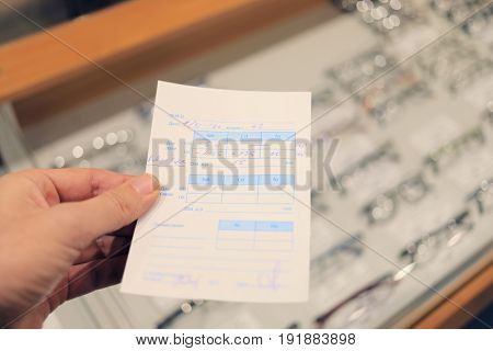 Hand holds doctor eyeglass prescription, text - date, age, distance, note