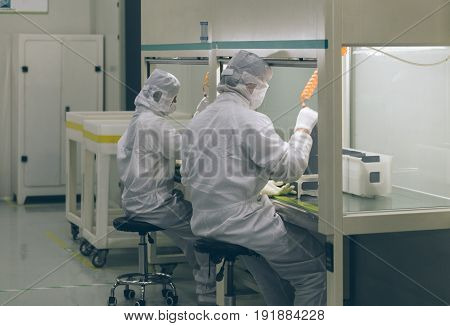 workers and machinery in a solar panel manufacturing industry factory.