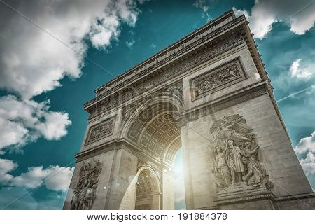 Arc de Triomphe in Paris under sky with clouds. One of symbols of France and one of the most popular tourist places in the world.