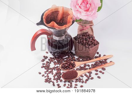 Coffee beans for drip coffee and black coffee in the glass jar coffee filter with flower and white background.