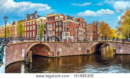 Channel in Amsterdam Netherlands Holland houses under river Amstel. Landmark old european city spring landscape.