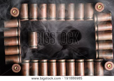 Frame Of Shot Gun Cartridges With One Lying Vertically In The Left Part With The Smoke