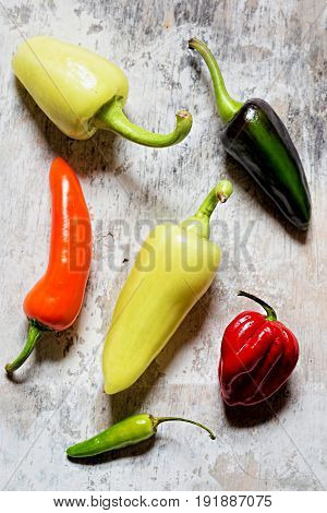 Green, red, yellow and orange peppers on white background